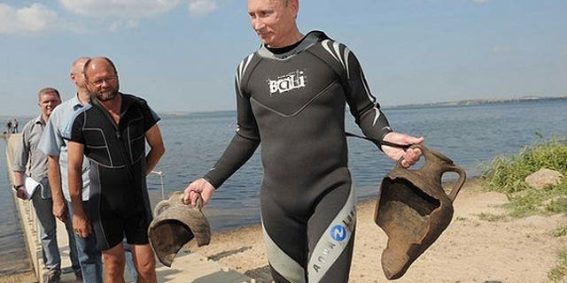 Russian Prime Minister Vladimir Putin carries artifacts he recovered whilst diving at an archaeological site off the Taman peninsular in southern Russia.
