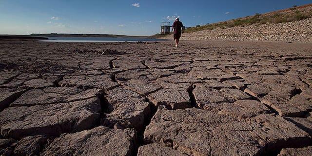 Aug. 7: Eddie Ray Roberts, superintendent of the city's waste and water department walks on the dried bed of Lake E.V. Spence in Robert Lee, Texas. After years of diminishing water supplies made even worse by the second most severe drought in state history, some communities are resorting to a plan that might have seemed absurd a generation ago: turning sewage into drinking water.