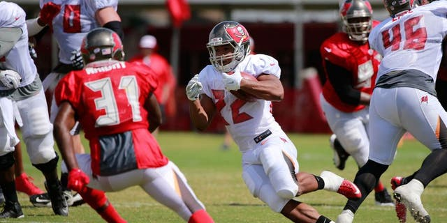 Aug 6, 2015; Tampa Bay, FL, USA; Tampa Bay Buccaneers running back Doug Martin (22) runs with the ball as Tampa Bay Buccaneers strong safety Major Wright (31) defends works out during training camp at One Buc Place. Mandatory Credit: Kim Klement-USA TODAY Sports