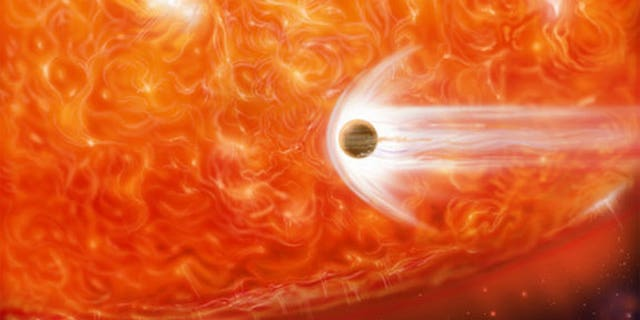 This artist's impression shows a red giant engulfing a Jupiter-like planet as it expands.