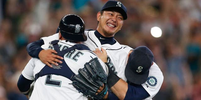 Aug 12, 2015; Seattle, WA, USA; Seattle Mariners pitcher Hisashi Iwakuma (18, center) celebrates with his teammates following the final out of his no-hit, 3-0 victory against the Baltimore Orioles at Safeco Field. Mandatory Credit: Joe Nicholson-USA TODAY Sports
