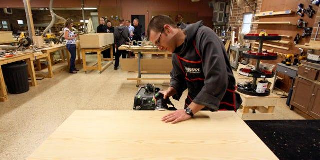 Aug. 12: Benedictine Novice Joseph Eichorn sands a casket lid in a workshop at St. Joseph Abbey in Covington, La.