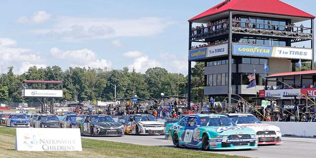 LEXINGTON, OH - AUGUST 15: Chris Buescher, driver of the #60 Zest Ford, and Alex Tagliani, driver of the #22 Discount Tire Ford, lead the field through the start/finish line for the start of the NASCAR Xfinity Nationwide Children's Hospital 200 at Mid-Ohio Sports Car Course on August 15, 2015 in Lexington, Ohio. Photo by Kirk Irwin/Getty Images)