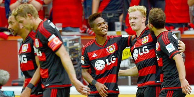 Leverkusen's midfielder Julian Brandt (2nd R) celebrates with Leverkusen's Swiss forward Admir Mehmedi (R) and Leverkusen's Brazilian defender Wendell after scoring 2-1 during the German first division Bundesliga football match Bayer 04 Leverkusen vs TSG 1899 Hoffenheim in Leverkusen, western Germany, on August 15, 2015. AFP PHOTO / SASCHA SCHUERMANN RESTRICTIONS: DURING MATCH TIME: DFL RULES TO LIMIT THE ONLINE USAGE TO 15 PICTURES PER MATCH AND FORBID IMAGE SEQUENCES TO SIMULATE VIDEO. == RESTRICTED TO EDITORIAL USE == FOR FURTHER QUERIES PLEASE CONTACT DFL DIRECTLY AT + 49 69 650050. (Photo credit should read SASCHA SCHUERMANN/AFP/Getty Images)