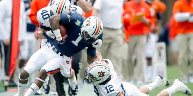 AUBURN, AL - APRIL 19: Linebacker Daniel Pond #40 and defensive back Mack VanGorder #12 of the Auburn Tigers attempts to tackle wide receiver D'haquille Williams #1 of the Auburn Tigers during Auburn's A-Day game on April 19, 2014 at Jordan-Hare Stadium in Auburn, Alabama. The blue team defeated the white team 58-3. (Photo by Michael Chang/Getty Images)