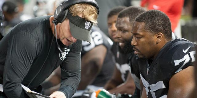 Aug 28, 2014; Oakland, CA, USA; Oakland Raiders defensive coordinator Jason Tarver speaks with defensive end Shelby Harris (75) during the third quarter of the game against the Seattle Seahawks at O.co Coliseum. Mandatory Credit: Ed Szczepanski-USA TODAY Sports