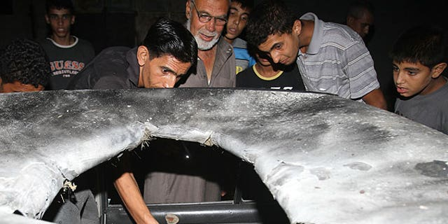 Aug. 21: Palestinians inspect the wreckage of a car after it was hit by an Israeli missile strike in Beit Lahia, northern Gaza Strip.