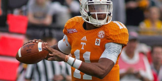 Jan 2, 2015; Jacksonville, FL, USA; Tennessee Volunteers quarterback Joshua Dobbs (11) looks for a receiver in the first quarter of the 2015 TaxSlayer Bowl against the Iowa Hawkeyes at EverBank Field. The Tennessee Volunteers beat the Iowa Hawkeyes 45-28. Mandatory Credit: Phil Sears-USA TODAY Sports