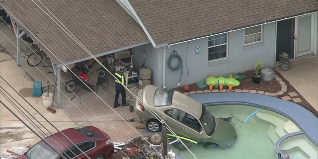 Police respond after a car crashed into a pool in Arlington, Texas Wednesday.