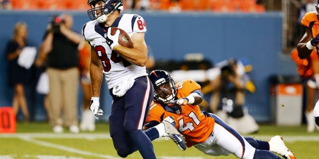 Aug 23, 2014; Denver, CO, USA; Houston Texans tight end Ryan Griffin (84) avoids the tackle of Denver Broncos defensive back Charles Mitchell (41) to run for a touchdown in the fourth quarter at Sports Authority Field at Mile High. The Texans defeated the Broncos 18-17. Mandatory Credit: Isaiah J. Downing-USA TODAY Sports