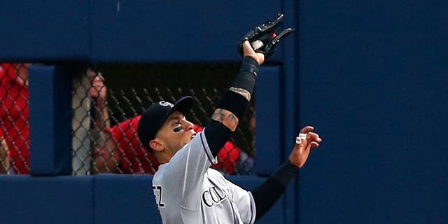 ATLANTA, GA - AUGUST 24: Right fielder Carlos Gonzalez #5 of the Colorado Rockies makes a sliding catch in the third inning during the game against the Atlanta Braves at Turner Field on August 24, 2015 in Atlanta, Georgia. (Photo by Mike Zarrilli/Getty Images)