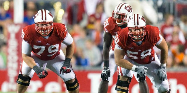 Sep 15, 2012; Madison, WI, USA; Wisconsin Badgers offensive linemen Ryan Groy (79) and Rick Wagner (58) line up for a play during the game against the Utah State Aggies at Camp Randall Stadium. Wisconsin defeated Utah State 16-14. Mandatory Credit: Jeff Hanisch-USA TODAY Sports