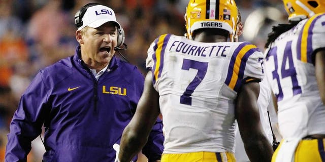 Oct 11, 2014; Gainesville, FL, USA; LSU Tigers head coach Les Miles congratulates running back Leonard Fournette (7) after he scored a touchdown against the Florida Gators during the second half at Ben Hill Griffin Stadium. LSU Tigers defeated the Florida Gators 30-27. Mandatory Credit: Kim Klement-USA TODAY Sports