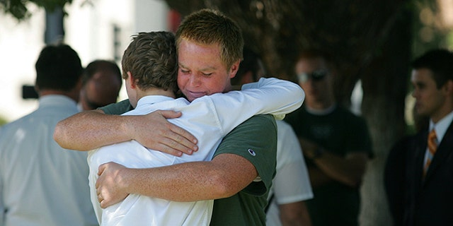 Aug. 29: Stephen Henriksen, right, gets a hug from fellow church member Ryan Henshaw after a shooting that killed lay bishop Clay Sannar of the Church of Jesus Christ of Latter-Day Saints in Visalia, Calif.