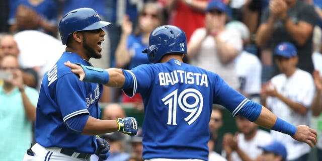 TORONTO, CANADA - AUGUST 29: Edwin Encarnacion #10 of the Toronto Blue Jays is congratulated by Jose Bautista #19 after hitting a three-run home run in the first inning during MLB game action against the Detroit Tigers on August 29, 2015 at Rogers Centre in Toronto, Ontario, Canada. (Photo by Tom Szczerbowski/Getty Images)