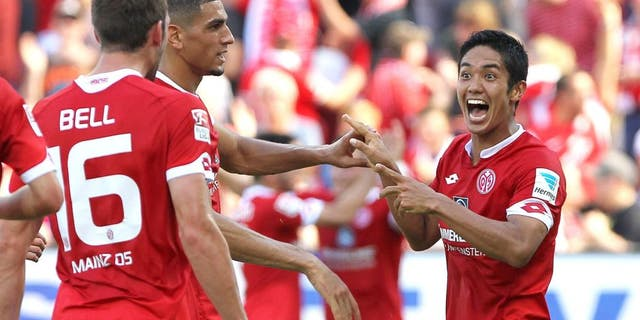 Mainz' Japanese striker Yoshinori Muto (R) celebrates scoring the 2-0 with teammates during the German first division Bundesliga football match 1 FSV Mainz 05 vs Hannover 96 in Mainz, Germany, on August 29, 2015. AFP PHOTO / DANIEL ROLAND RESTRICTIONS: DURING MATCH TIME: DFL RULES TO LIMIT THE ONLINE USAGE TO 15 PICTURES PER MATCH AND FORBID IMAGE SEQUENCES TO SIMULATE VIDEO. == RESTRICTED TO EDITORIAL USE == FOR FURTHER QUERIES PLEASE CONTACT DFL DIRECTLY AT + 49 69 650050. (Photo credit should read DANIEL ROLAND/AFP/Getty Images)