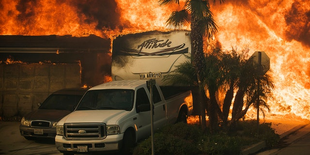 Flames consume a home on Via Arroyo as a wildfire rages in Ventura, California, Tuesday