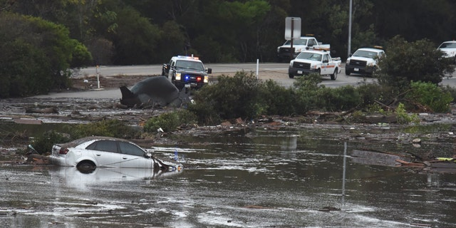 An abandoned car floats in flooded waters and debris on the freeway after a mudslide in Montecito.