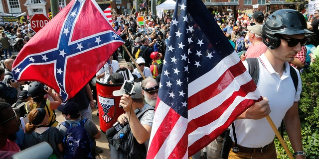 White nationalist demonstrators walk into a park surrounded by counter-protesters.