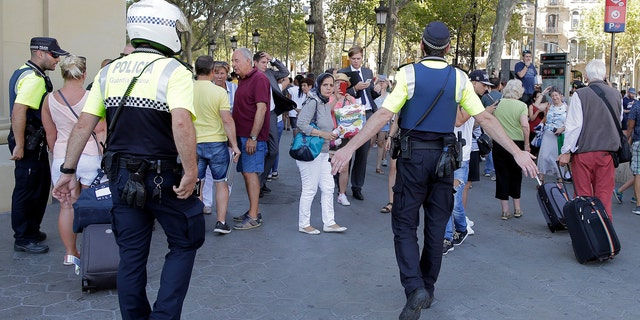 Police officers tell members of the public to leave the scene in a street in Barcelona, Spain, Thursday, Aug. 17, 2017. Police in the northern Spanish city of Barcelona say a white van has jumped the sidewalk in the city's historic Las Ramblas district, injuring several people. (AP Photo/Manu Fernandez)