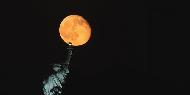 JERSEY CITY, NJ - JUNE 11: The moon rises behind the Statue of Liberty in New York City on June 11, 2017 as seen from Jersey City, NJ. (Photo by Gary Hershorn)