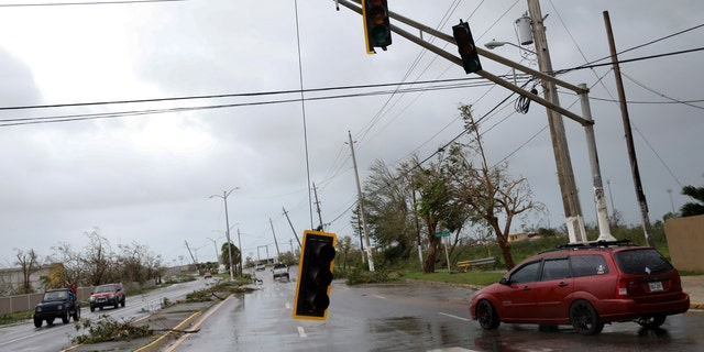 Cars drive past a damaged traffic light after the area was hit by Hurricane Maria en Guayama, Puerto Rico September 20, 2017.