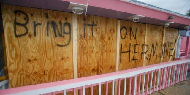 A hand painted sign on a boarded up bar is seen as Hurricane Hermine nears the Florida coast, Thursday, Sept. 1, 2016, in Cedar Key, Fla.