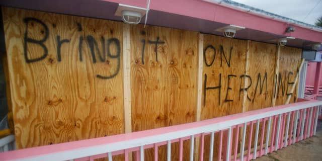 A hand painted sign on a boarded up bar is seen as Hurricane Hermine nears the Florida coast, Thursday, Sept. 1, 2016, in Cedar Key, Fla.