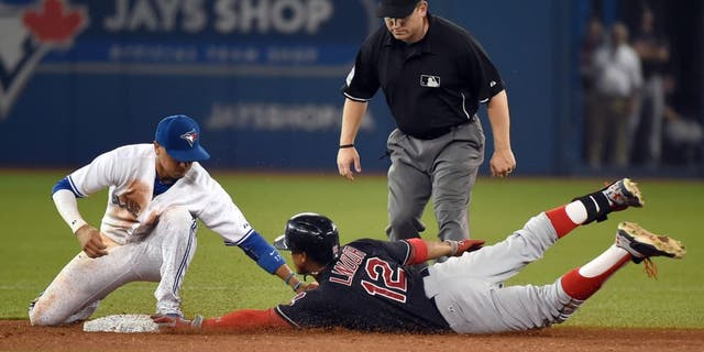 Sep 1, 2015; Toronto, Ontario, CAN; Cleveland Indians shortstop Francisco Lindor (12) slides safely into second with a double ahead of a tag from Toronto Blue Jays second baseman Ryan Goins (17) in the ninth inning at Rogers Centre.The Jays won 5-3. Mandatory Credit: Dan Hamilton-USA TODAY Sports