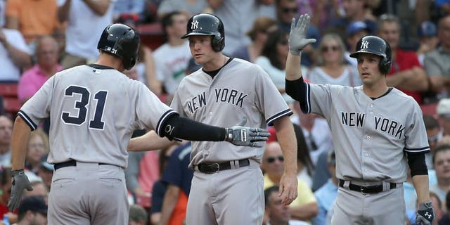 BOSTON, MA - SEPTEMBER 2: Greg Bird #31 of the New York Yankees is greeted by Chase Headley #12 and John Ryan Murphy #66 after his home run in the second inning against he Boston Red Sox at Fenway Park on September 2, 2015 in Boston, Massachusetts. (Photo by Jim Rogash/Getty Images)
