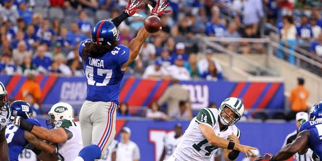 Aug 29, 2015; East Rutherford, NJ, USA; New York Jets quarterback Ryan Fitzpatrick (14) throws a pass while being defended by New York Giants linebacker Devin Unga (47) during the first half at MetLife Stadium. Mandatory Credit: Ed Mulholland-USA TODAY Sports