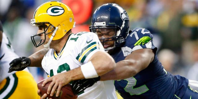 Sep 4, 2014; Seattle, WA, USA; Seattle Seahawks defensive end Michael Bennett (72) forces a fumble by Green Bay Packers quarterback Aaron Rodgers (12) during the third quarter at CenturyLink Field. The fumbles was recovered by Green Bay in the end zone for a safety. Mandatory Credit: Joe Nicholson-USA TODAY Sports