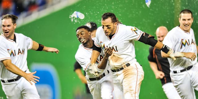 Sep 4, 2015; Miami, FL, USA; Miami Marlins third baseman Martin Prado (14) celebrates with Miami Marlins second baseman Dee Gordon (left) after Prado hit the game winning RBI single to defeat the New York Mets 6-5 in 11 inning at Marlins Park. Mandatory Credit: Steve Mitchell-USA TODAY Sports
