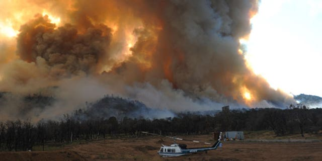 Sept. 4: A damaged helicopter sits as a large wildfire burns to the southwest of Tehachapi, Calif.