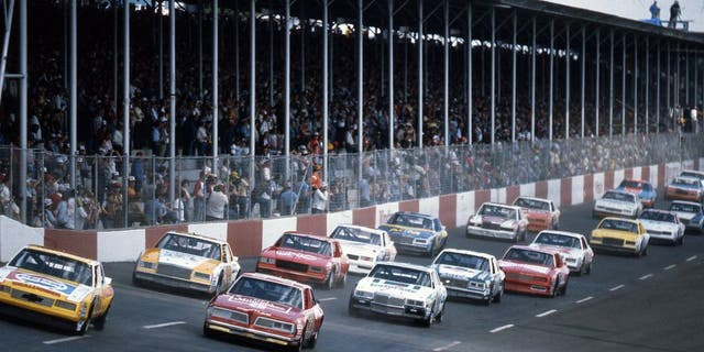 DARLINGTON, SC - APRIL 10, 1983: Darrell Waltrip (No. 11) pulls ahead of pole sitter Tim Richmond (No. 27) as the field heads toward turn one at the start of the TranSouth 500 at Darlington Raceway. (Photo by ISC Images & Archives via Getty Images)