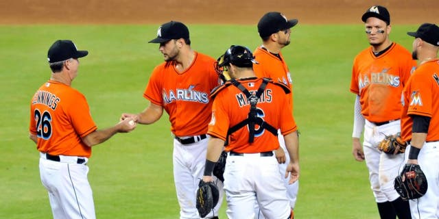 Sep 6, 2015; Miami, FL, USA; Miami Marlins manager Dan Jennings (left) takes starting pitcher Jarred Cosart (center) out of the game during the fifth inning against the New York Mets at Marlins Park. Mandatory Credit: Steve Mitchell-USA TODAY Sports