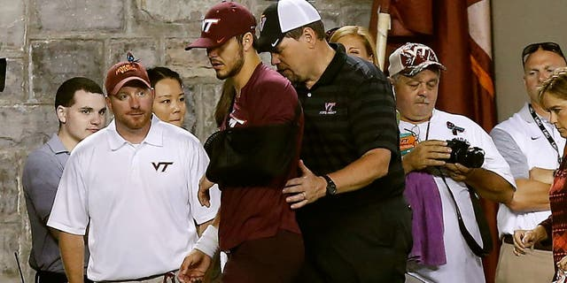 Sep 7, 2015; Blacksburg, VA, USA; Virginia Tech Hokies quarterback Michael Brewer (middle) leaves the field with his left arm in a sling after being injured against the Ohio State Buckeyes in the third quarter at Lane Stadium. Mandatory Credit: Geoff Burke-USA TODAY Sports