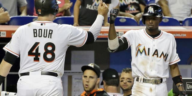 Miami Marlins' Justin Bour (48) celebrates with Dee Gordon (9) after scoring after Donovan Solano hit into a double play during the fifth inning of a baseball game against the Milwaukee Brewers, Monday, Sept. 7, 2015, in Miami. (AP Photo/Wilfredo Lee)