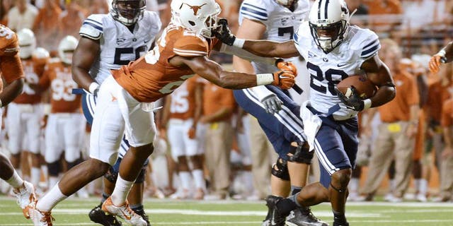 Sep 6, 2014; Austin, TX, USA; Brigham Young Cougars running back Adam Hine (28) runs for a touchdown against Texas Longhorns safeties Adrian Colbert (l) and Mykkele Thompson (2) during the second half at Darrell K Royal-Texas Memorial Stadium. BYU beat Texas 41-7. Mandatory Credit: Brendan Maloney-USA TODAY Sports
