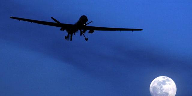 A U.S. Predator drone flies over the moon above Kandahar Air Field, Afghanistan.