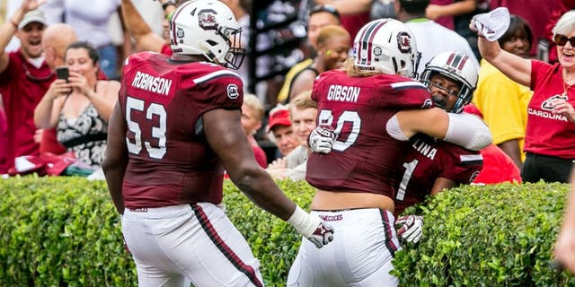 Sep 13, 2014; Columbia, SC, USA; South Carolina Gamecocks offensive tackle Corey Robinson (53) and tight end Cody Gibson (90) and wide receiver Pharoh Cooper (11) celebrate a touchdown by Cooper against the Georgia Bulldogs in the first quarter at Williams-Brice Stadium. Mandatory Credit: Jeff Blake-USA TODAY Sports