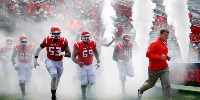 Rutgers coach Chris Ash, right, leads his players onto the field before a NCAA college football game against Howard Saturday, Sept. 10, 2016, in Piscataway, N.J.