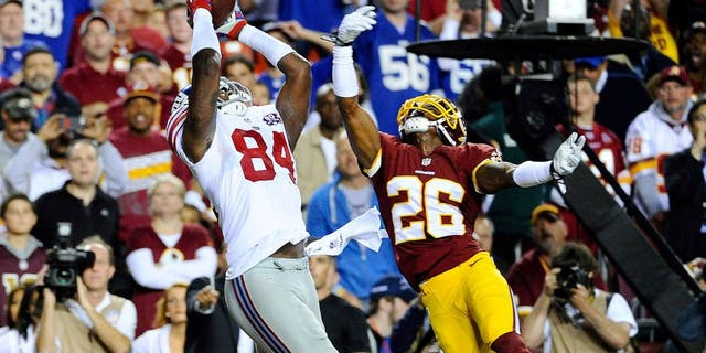 Sep 25, 2014; Landover, MD, USA; New York Giants tight end Larry Donnell (84) catches a touchdown pass as Washington Redskins strong safety Bashaud Breeland (26) defends during the first half at FedEx Field. Mandatory Credit: Brad Mills-USA TODAY Sports