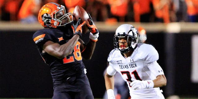 Sep 25, 2014; Stillwater, OK, USA; Oklahoma State Cowboys wide receiver James Washington (28) makes a catch in front of Texas Tech Red Raiders defensive back Justis Nelson (31) during the third quarter of a game at Boone Pickens Stadium. Oklahoma State won 45-35. Mandatory Credit: Alonzo Adams-USA TODAY Sports