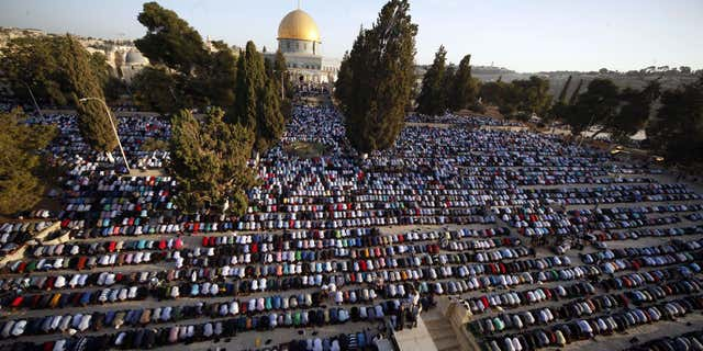 FILE - In this Thursday, Sept. 24, 2015. file photo, Palestinians pray during the Muslim holiday of Eid al-Adha, near the Dome of the Rock Mosque.