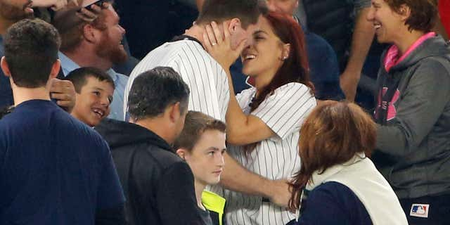 Sept. 27, 2016: Andrew Fox and Heather Terwilliger embrace after getting engaged during a baseball game between the New York Yankees and the Boston Red Sox in New York.