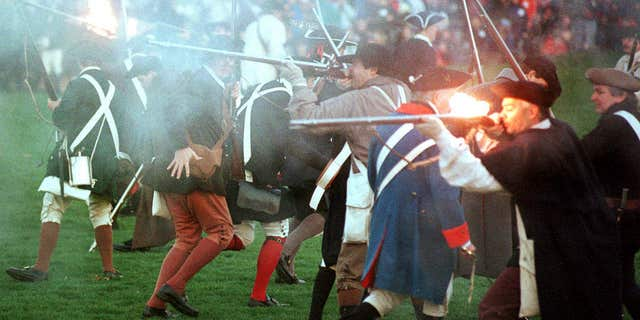 FILE - In this April 15, 2000, file photo, Revolutionary War re-enactors portraying colonial militiamen fire on British regular soldiers in the Battle of Lexington on the Lexington Green in Lexington, Mass.