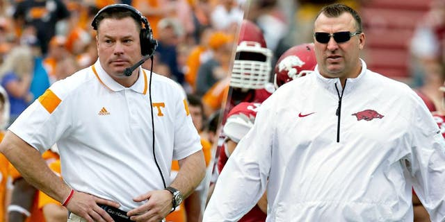 JACKSONVILLE, FL - JANUARY 02: Head coach Butch Jones of the Tennessee Volunteers watches the action during the TaxSlayer Bowl against the Iowa Hawkeyes at EverBank Field on January 2, 2015 in Jacksonville, Florida. (Photo by Sam Greenwood/Getty Images) FAYETTEVILLE, ARKANSAS - APRIL 26: Head Coach Bret Bielema of the Arkansas Razorbacks watches his team warm up before the Red White Spring Football game at Razorback Stadium on April 26, 2014 in Fayetteville, Arkansas. (Photo by Wesley Hitt/Getty Images)