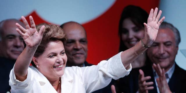 Brazil's President Dilma Rousseff, raises her arms to acknowledge the crowd during her acceptance speech at a press conference in a hotel in Brasilia, Brazil, Sunday, Oct. 26, 2014. Official results showed Sunday that President Rousseff defeated opposition candidate Aecio Neves of the Brazilian Social Democracy Party, and was re-elected Brazil's president. (AP Photo/Eraldo Peres)