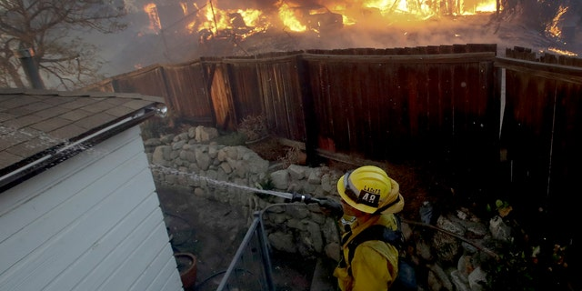 A Los Angeles County firefighter puts water on a burning roof during a wildfire in the Lake View Terrace area of Los Angeles, Tuesday.